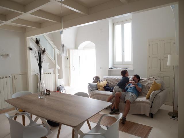 Vista del salón comedor en blanco y madera con hombre y niño en el sofá