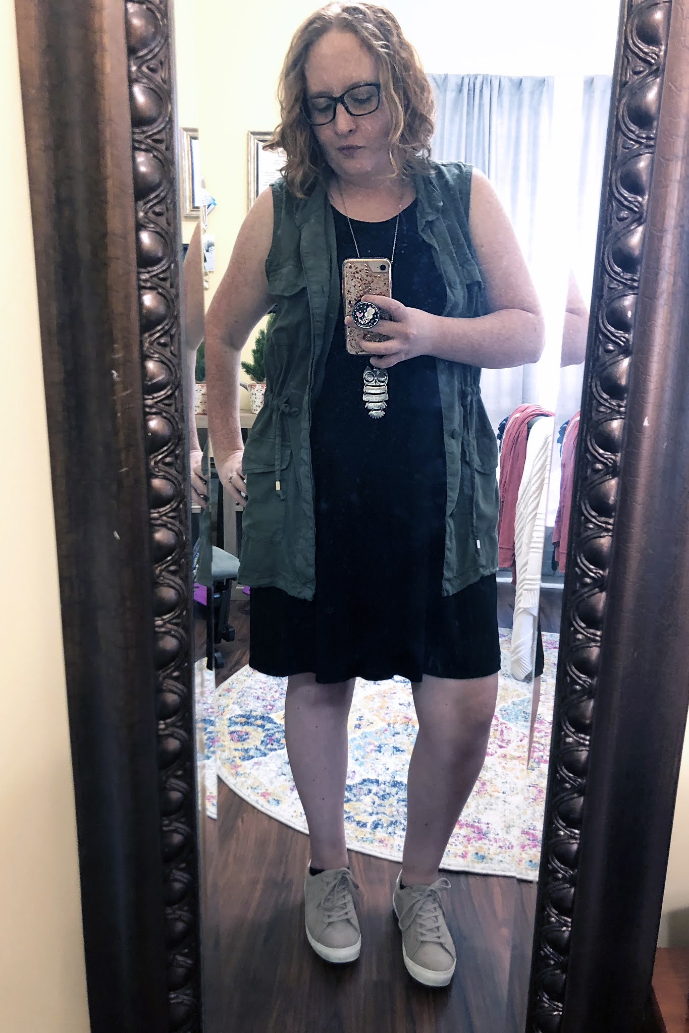 black dress with utility vest and neutral sneakers