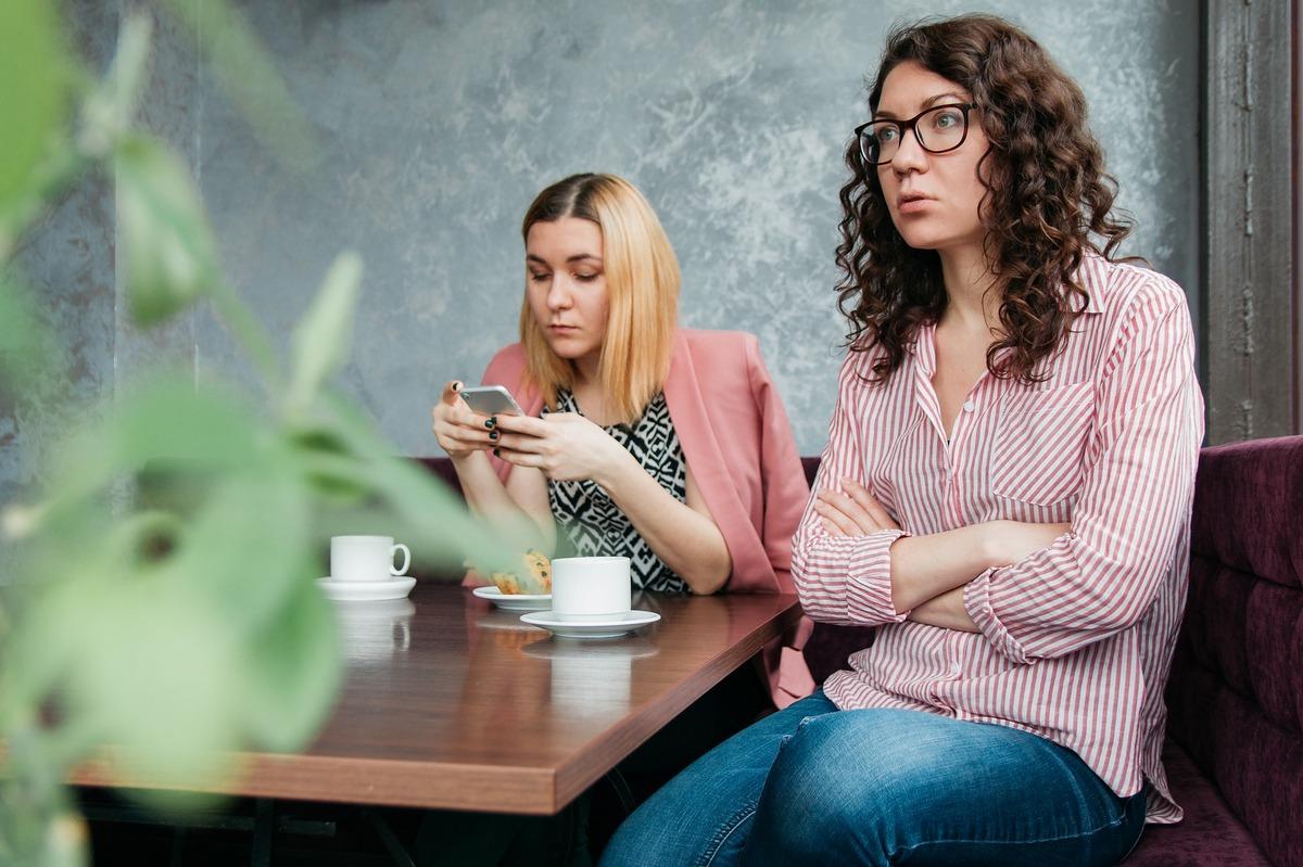 dwie kobiety siedzą przy stole, każda zajęta swoimi sprawami