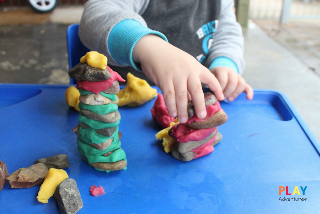 Buidling playdough and rock towers next to each other