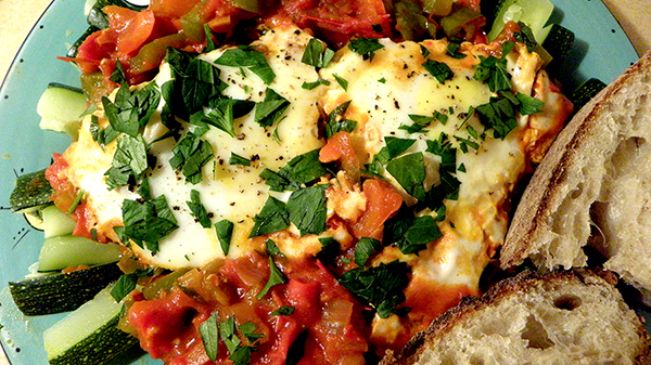 Plate of shakshuka served over zucchini spears with crusty bread