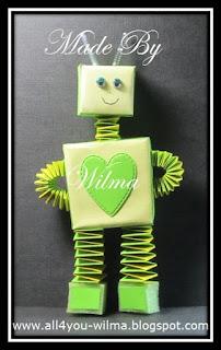 Een groene robot gemaakt van muizentrappetjes, vouwblaadjes en wiebeloogjes. A green robot made of accordion papercrafts, thin paper and wiggle eyes.