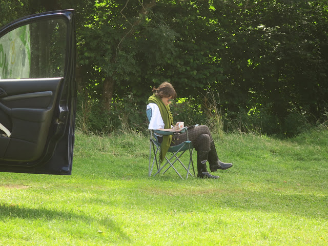 Woman reading kindle, wearing sunglasses and scarf while drinking tea. On a foldout chair by car.