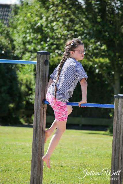 Mädchen mit Down-Syndrom auf Klettergerüst