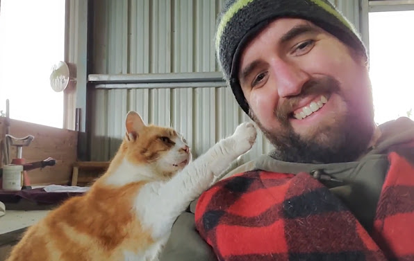 Barn cat taps man on face for more petting please