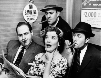 "Nanette Fabray, seated at right, gagged as railroad commuters Sid Caesar, left, Carl Reiner, top, center, and Howard Morris poked their smokes in her direction while looking over her shoulder to read her newspaper, on ""Caesar's Hour,"" April 27, 1955."