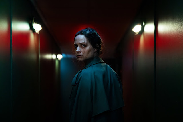 A woman stands in dimly lit hallway