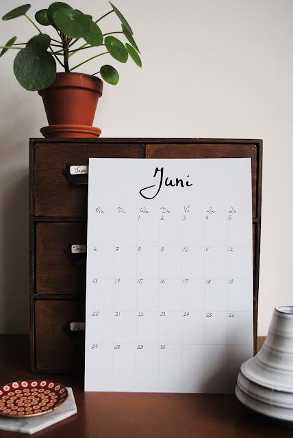 A4 met daarop de kalender van de maand juni gestyled met een houten kastje en keramieken vaasjes.