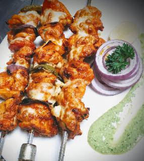Chicken cheese kebab Shewer on a serving plate with green chutney and onion slices