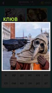 мужчина в маске с клювом держит в руке ворону с открытым клювом