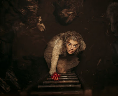 "Samara Weaving, wearing her dirty wedding dress, crawls out of a pit in a movie still for the 2019 horror film ""Ready or Not"""