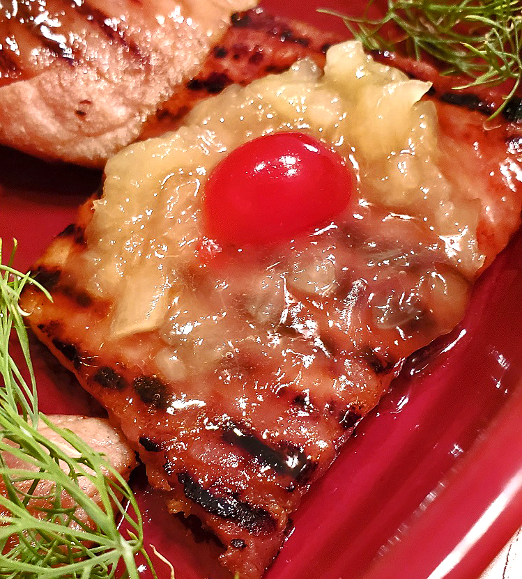 this is a ham steak with a pineapple glaze grilled with a cherry on top