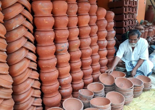 old man sitting beside pots