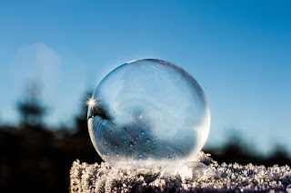 A frozen bubble rests on a frosty stone or log, catching the light.