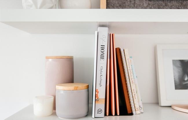 livros e revistas organizados em uma prateleira clean feminina