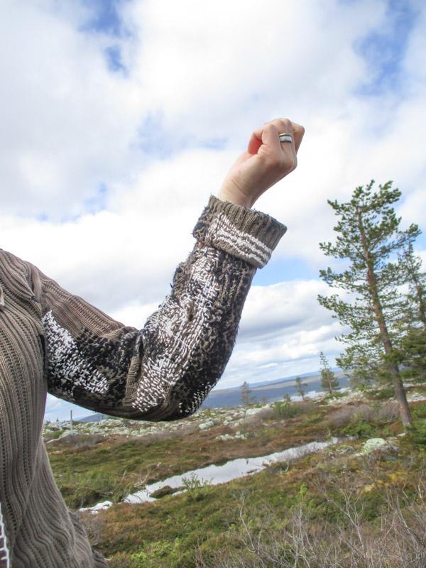 Ikuiset neuletakin hihan korjaukset valkoisella ja mustalla puuvillalangalla, taustalla Särkitunturin maisemia