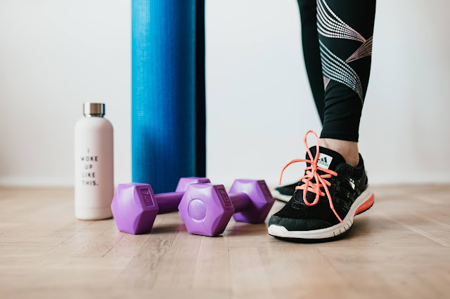 A drinks bottle, yoga mat & dumbells lined up in a row next to a person in trainers