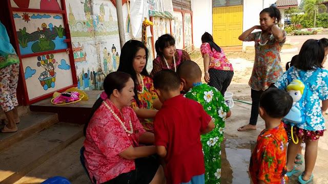 niños ofreciendo guirnaldas y el agua a sus maestras