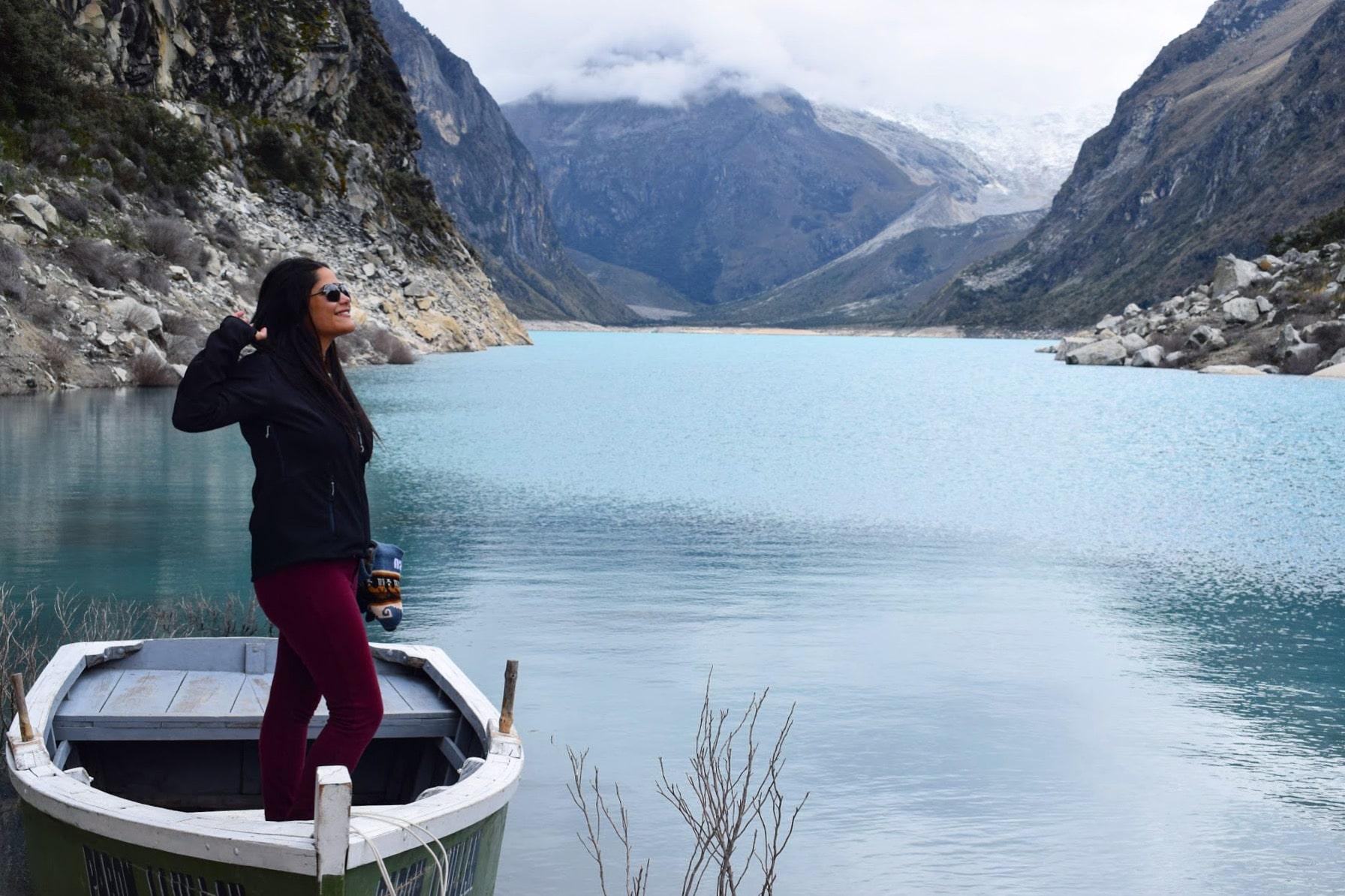 mulher morena em um barco a remo em um lago azul