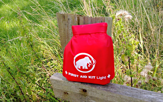 First aid kit, sitting on a gate post.