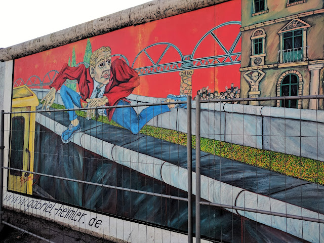 East Side Gallery - painted wall with a man jumping the wall