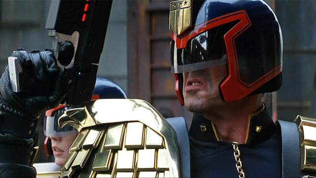 Sylvester Stallone in Judge Dredd costume, holding Lawgiver gun