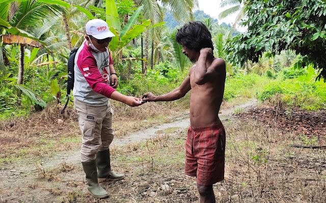 Salah Satu Komisoner KPU Tikep saat berbincang sambil memberikan rokok kepada warga suku Tugutil