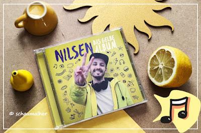 gelbe Utensilien wie Malkreide, Zitrone, Holzsonne und eine Tasse passen zum gelben Album