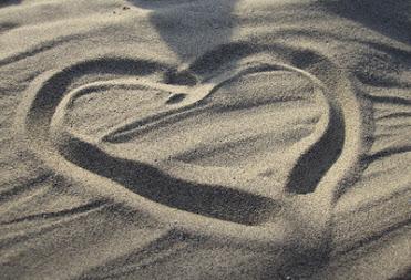 Ein Herz in den Sandboden gezeichnet als Zeichen des liebevollen Mitgefühls