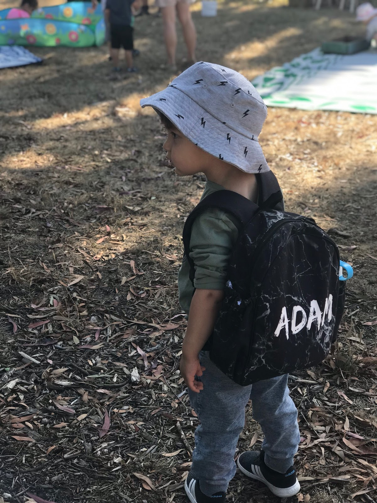 Image is a photo of a mixed race Asian toddler walking away from the camera outdoors. He is wearing a backpack with black marble print and white text spelling ADAM. He is also wearing a grey wide brim hat and a long sleeve green top, with blue jeans and black sneakers. He is looking at something off-camera, so the side profile of his face is visible. In the background, some colourful picnic mats are set up upon the ground.