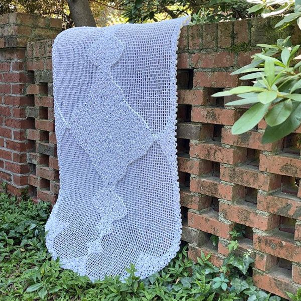 large-scale dimensional quilled paper lace displayed on brick wall