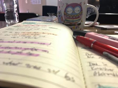 Notes in notebook, with coffee in background and Stabilo Boss highlighters