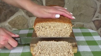 Slicing homemade honey wheat bread with a knife.