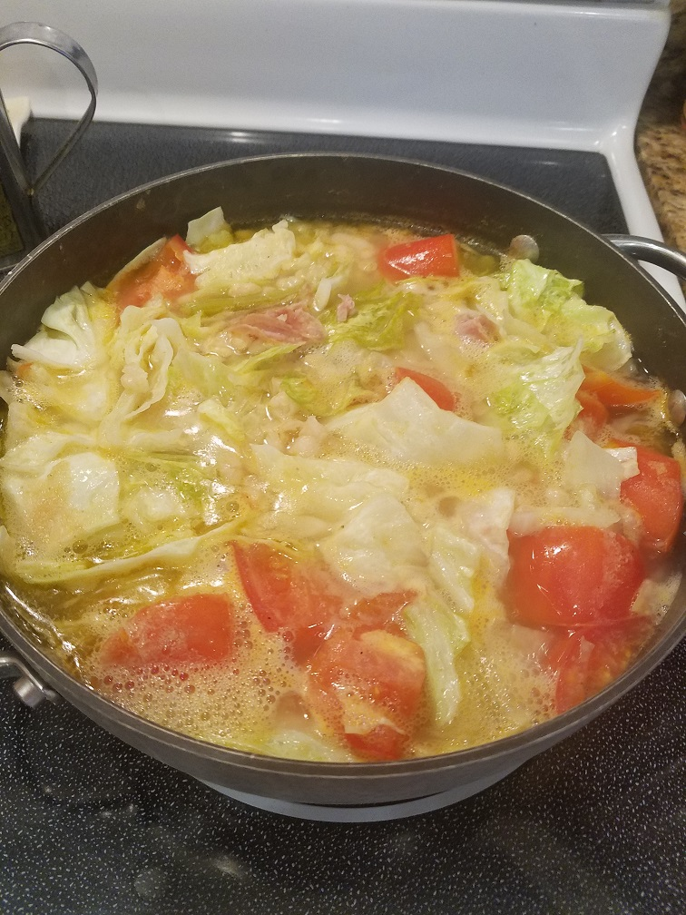 This is ham cabbage and white bean comfort soup. It has tomatoes, carrots and ham and vegetables all on top of stove in one pot