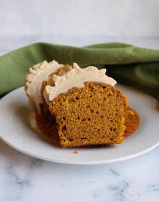 brown sugar frosting topped pumpkin cupcake cut in half with moist inside showing