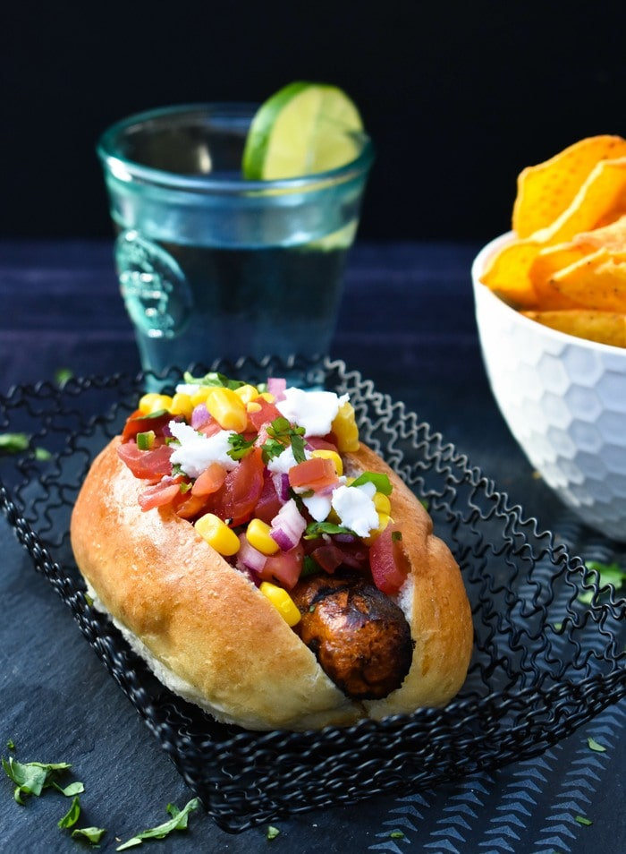 Vegan hot dog topped with Mexican salad toppings