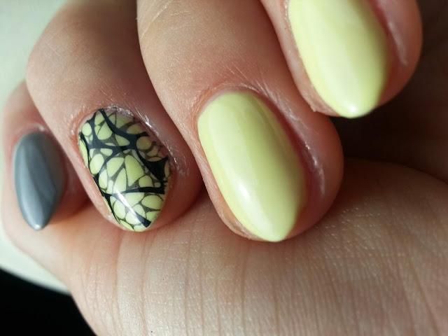 Żółte paznokcie z szarym akcentem i czarną pajęczynką