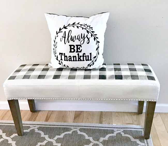 A painted fabric bench with a buffalo plaid stencil