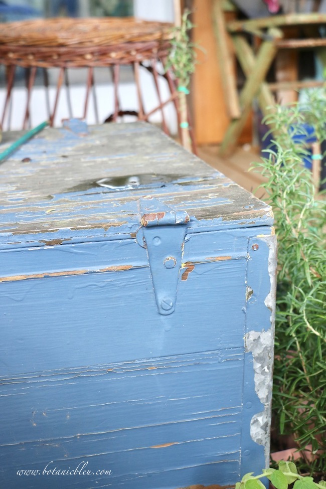 Rustic blue box on back porch with puddle of water on top