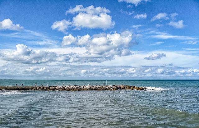 El mar gente pescando y el cielo cubierto de nubes
