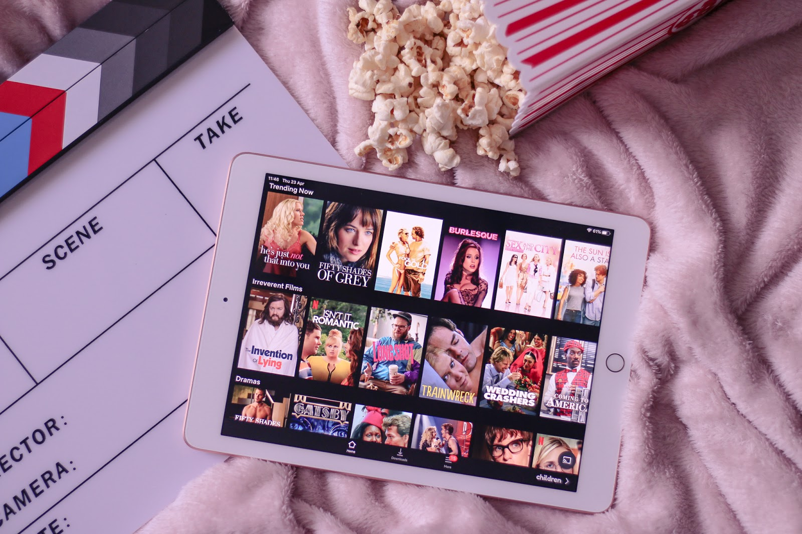 Flatlay photo of a rose gold iPad, Clap board and popcorn on top of a pink blanket