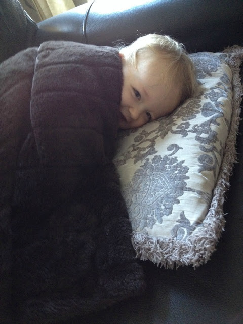 toddler lying on sofa head on cushion snuggled under blanket. shhh
