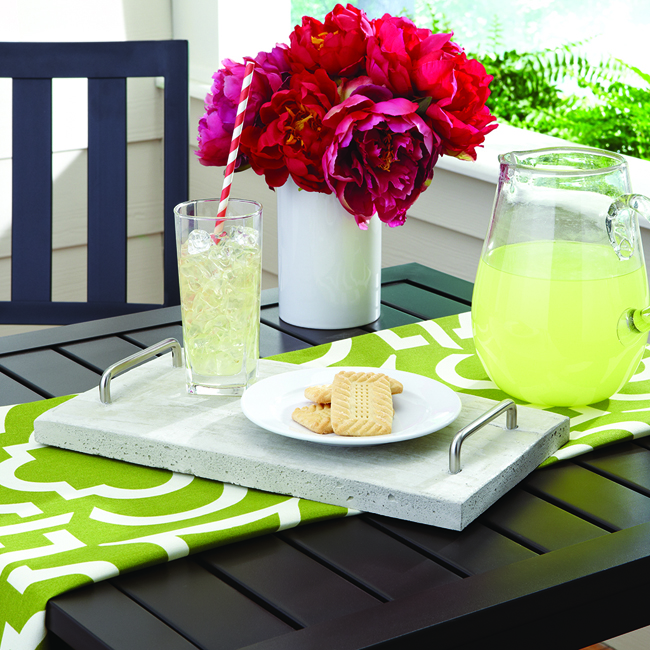 Concrete tray with silver handles serving lemonade and cookies with a bouquet of pink peonies and green runner on black table set