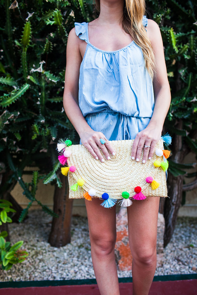 A cactus print romper with a bright pom pom clutch.