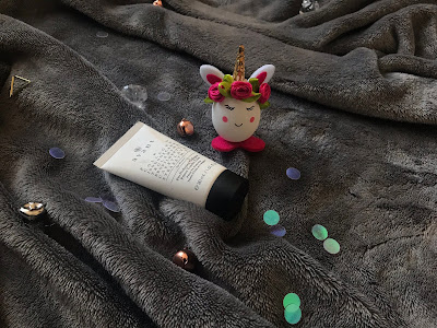 tube of primer on a blanket with a small unicorn toy