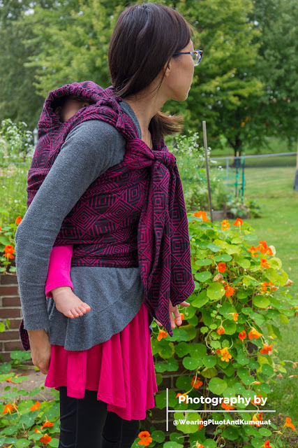 "[Image of a tan skin Asian woman with dark brown hair wearing a sleeping toddler on her back in a magenta and black concentric square patterned meh dai baby carrier. The toddler has on bright magenta leggings. The woman has on a magenta swing top and black capri leggings. They coincidentally super match today. They're outside at a raised garden overflowing with fresh green leaves and orange nasturtium blossoms. The woman is standing upright, looking into the distance. Bottom right corner in white is a watermark with a ""T"" lying on its side; top text ""Photography by,"" bottom text ""@WearingPluotAndKumquat.""]"