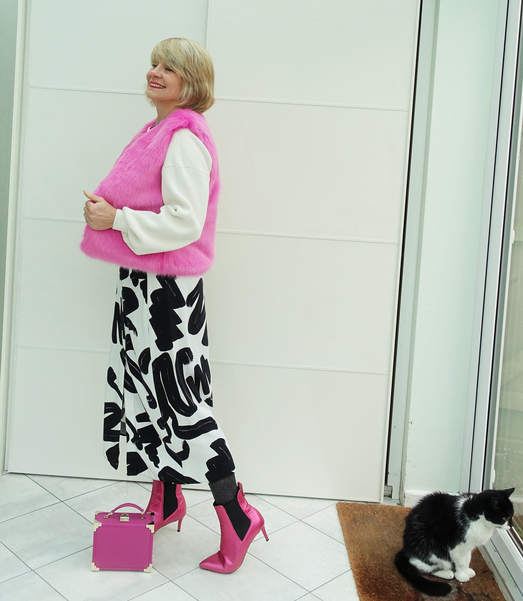 A faux fur pink gilet and pink boots liven up a black and white skirt and white top as Is This Mutton explores the different names for garments used in the UK and US