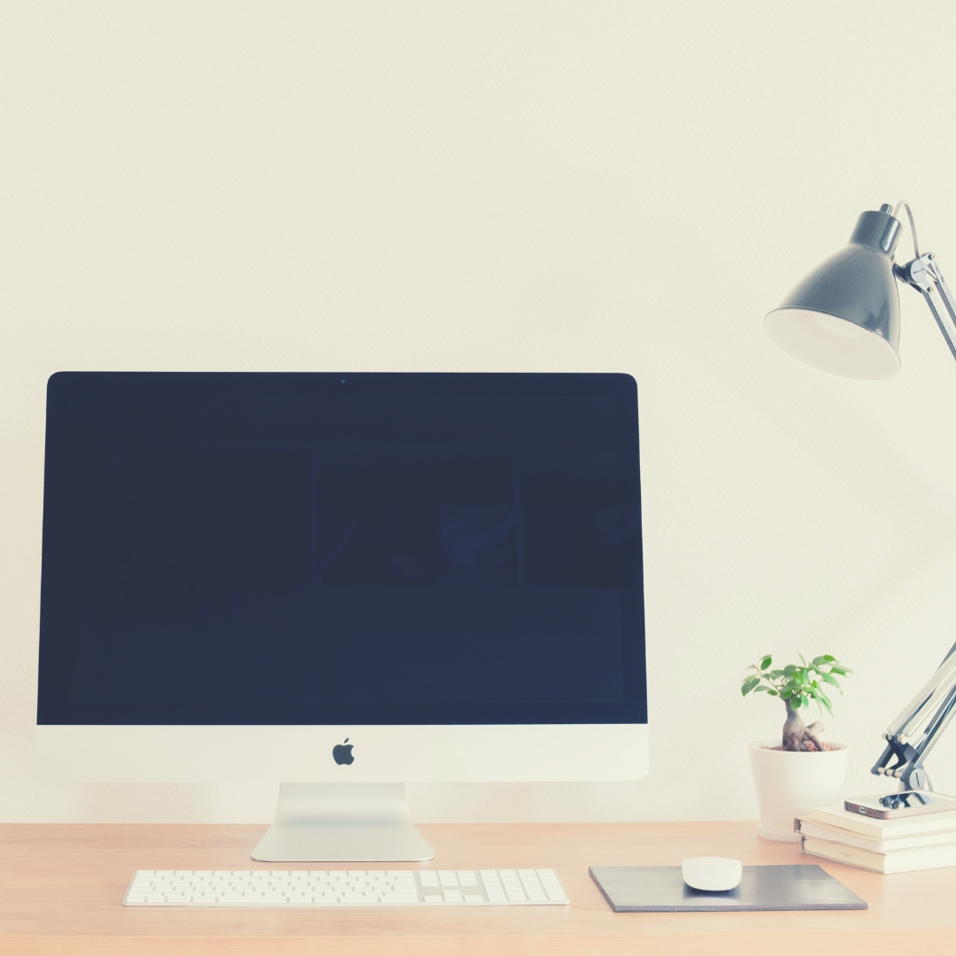 An iMac sits on a desk next to a desk lamp