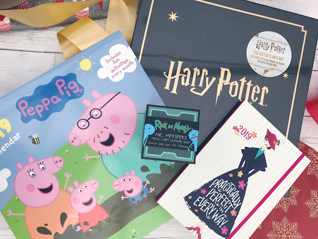 Peppa Pig calendar, Harry Potter gift set, Mary Poppins themed diary, Rick & Morty calendar cube, with wrapping paper and ribbon nearby