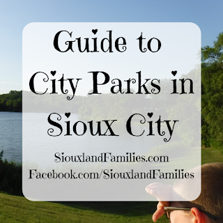 "in background, a small blue lake sits below a grassy hill, with forested area on the opposite shore, and a boy with blonde hair gazes at the water. in foreground, the words ""Guide to City Parks in Sioux City"" and ""SiouxlandFamilies.com Facebook.com/SiouxlandFamilies"""
